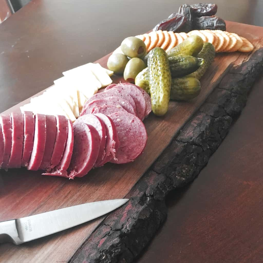 "I needed a flat place on my ottoman to put a cup of coffee. So I figured out How to Make a Live Edge Charcuterie Tray, so I also have an awesome ""small things"" food tray! #nerdymammablog #diy #charcuterie"
