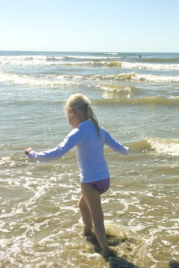 little girl running on a beach with waves to represent how to teach a preschooler to be a leader