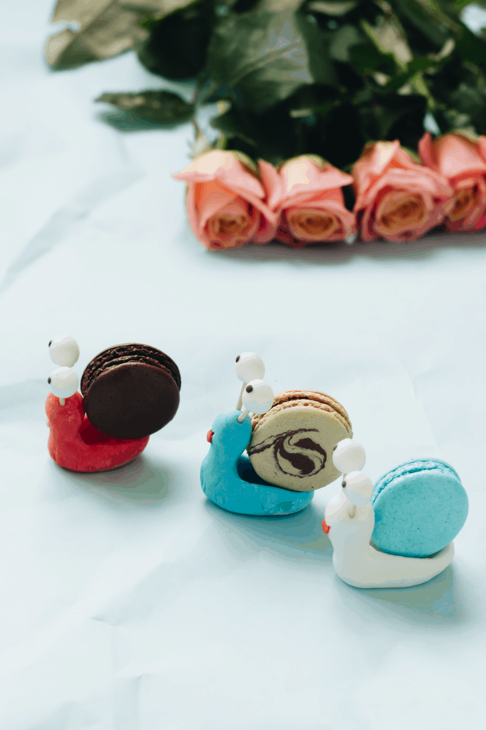 trio of snail macarons on a table to show a unique macaron decorating idea